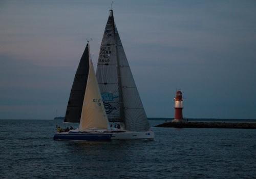 Spät Abends kommen die Yachten von ihrer Langstrecken-Wettfahrt durch das Ziel an der Mole von Warnemünde