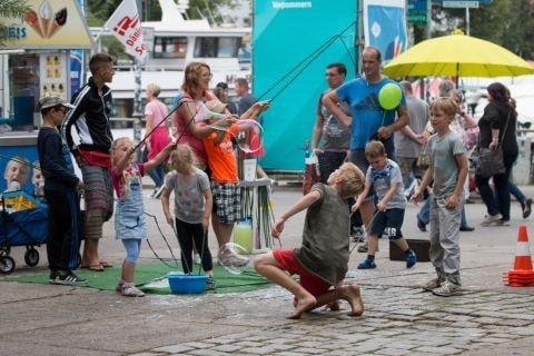 An der Brücke über dem Alten Strom probieren Kinder, besonders große Seifenblasen fliegen zu lassen